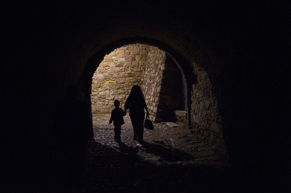 Inside the castle of Chios. A mother walks with her child towards a gate of the castle.