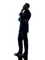 one caucasian business man standing thinking silhouette isolated on white background