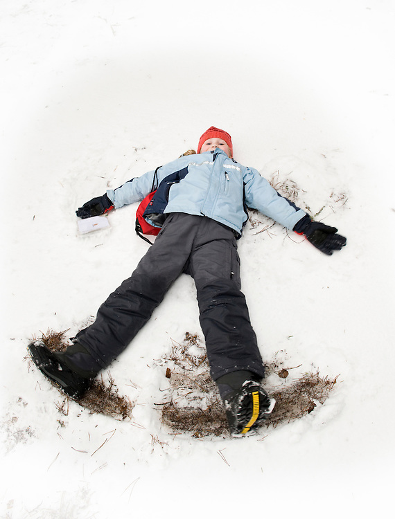 Estonian child making snow angels