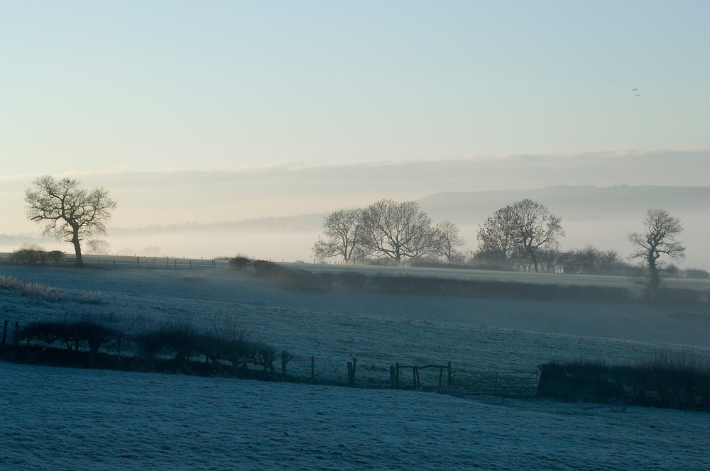 Mist over frost covered fields near the Peak District town of Ashbourne, Derbyshire, England, UK.