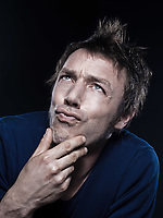 studio portrait on black background of a funny expressive caucasian man puckering pensive