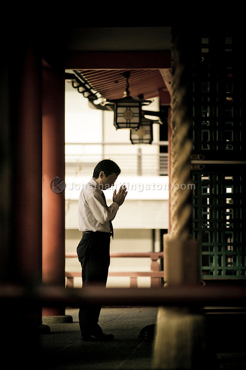 A businessman prays at the Ninomiya Shinto Shrine in Kobe, Japan.  The shrine is located in the heart of downtown and offers a peaceful respite from the commotion of the city.