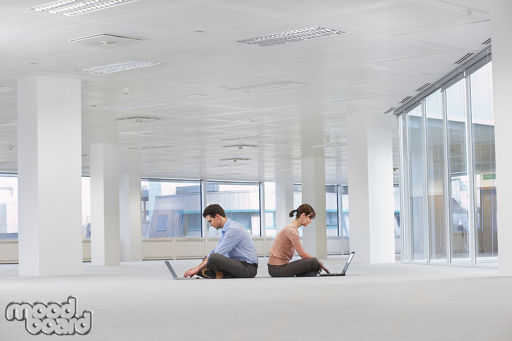 Two office workers sitting back to back using laptops on floor of empty office space