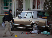 Police investigators at the scene of a drug related shoot out in a slum in Juarez, Mexico January 14, 2009, as the family view from behind the screen door. The shooting, believed linked to the ongoing drug war which has already claimed more than 40 people since the start of the year. More than 1600 people were killed in Juarez in 2008, making Juarez the most violent city in Mexico.    (Photo by Richard Ellis)