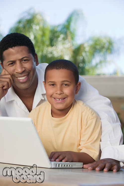 Father and Son sitting on patio Using Laptop portrait