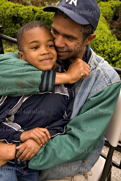 African American father sitting on bench holding his young son playfully, displaying caring and love.<br /> <br /> Release #2307