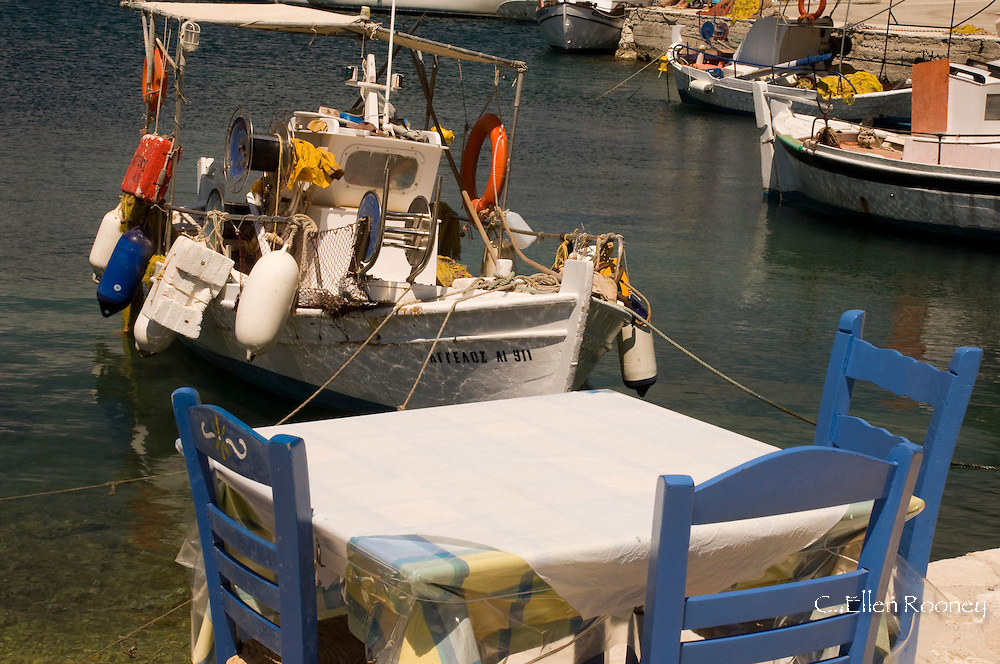 A taverna table on the waterfront next to a fishing boat in Frikes, Ithaca,<br /> The Ionian Islands, Greece