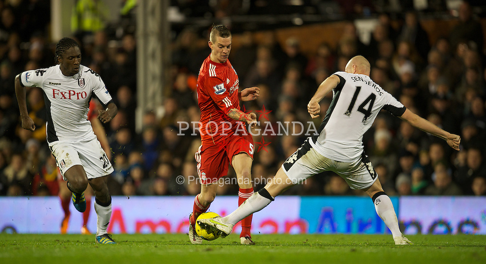 LONDON, ENGLAND - Monday, December 5, 2011: Liverpool's Daniel Agger is tackled by Fulham's Philippe Senderos during the Premiership match at Craven Cottage. (Pic by David Rawcliffe/Propaganda)