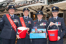 Covent Garden, London, October 30th 2014. They Royal British Legion's Poppy Day in London centred around Covent Garden where bands, choirs, classical and pop musicians entertained crowds as Air Force personnel carrying donation buckets sold poppies, hoping to raise in excess of £1 million. Pictured: Air Force personnel help bring in buckets full of donations from the public.