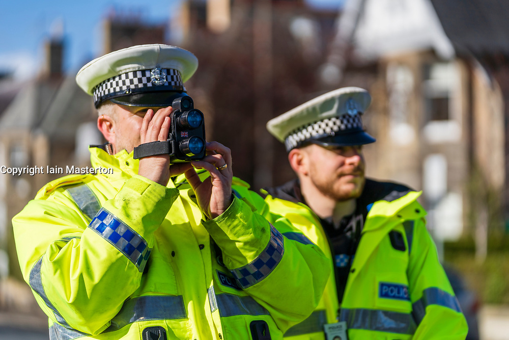 Edinburgh, Scotland, UK. 14 March, 2019. Police checking car speeds in Edinburgh at the first in a series of pilot 20mph 'Roadside Education' events, held in partnership with Police Scotland, aiming to raise awareness of the consequences of breaking 20mph speed limits. Speeding drivers will be stopped by Police Officers and offered a short driver education session in a Police Command Unit. This will involve Edinburgh Council Transport Officers, who will remind drivers of their speed, advising of the potential consequences of their actions and the impact this can have on the severity of a collision. Drivers will then be shown a short video featuring Edinburgh school children who asked the Council to help them reduce speeds around their school. Similar initiatives have previously been carried out in Liverpool and Birmingham