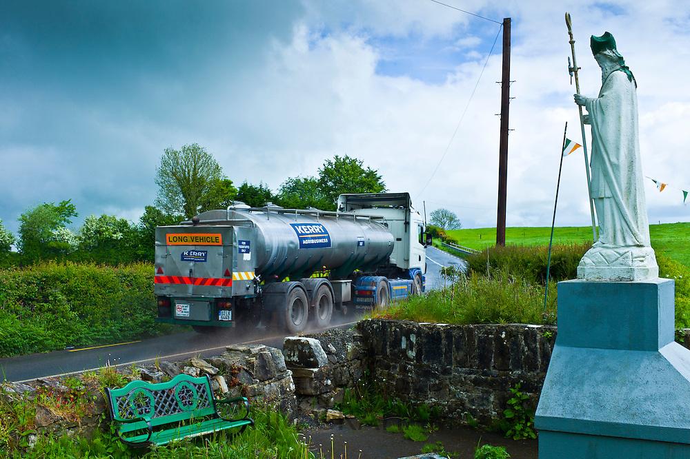 Milk tanker lorry passes religious shrine of Irish patron saint St Patrick in Ballingarry, County Limerick, Ireland