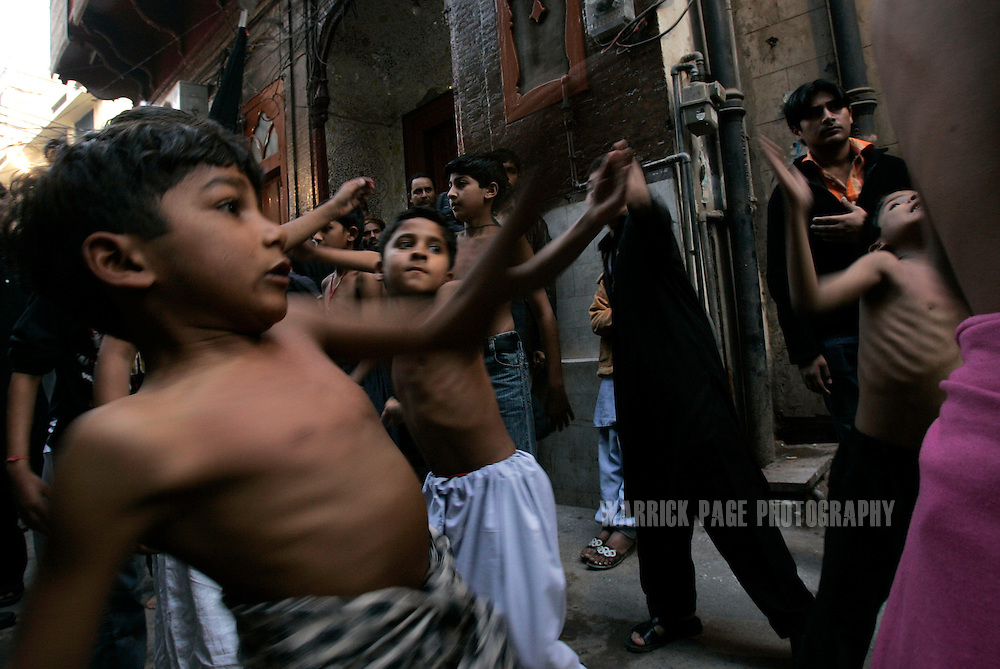 LAHORE, PAKISTAN - JANUARY 29: Children beat their chests during an Ashura ritual in the Old City, Lahore, Pakistan on Monday 29 January, 2007. Shiite Muslims around the world commemorate the martyrdom of the Prophet Mohammed's grandson, Imam Hussein, who was killed during the battle of Karbala, Iraq. Security has been increased throughout Pakistan due to fears of sectarian violence after suicide bombings in Islamabad and Peshawar last week claimed the lives of 15 people. (Photo by Warrick Page)