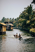 Alleppey, India -- February 20, 2018: Boats slowly make their way through the serene backwaters of southern Kerala.