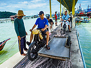 23 AUGUST 2018 - TELUK BAHANG, PENANG, MALAYSIA: A motorcycle that hauls supplies to fishing trawlers returns to the port in Teluk Bahang on the island of Penang. Fishermen on Penang, an island off the west coast of mainland Malaysia, are being pressured by the island's resort development and reduce catches in the waters off Malaysia.     PHOTO BY JACK KURTZ