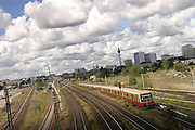 An S-bahn train shoots pass eastern Berlin with skyline in the background, under a blanket of clouds. ..Picture taken 2005 by Justin Jin
