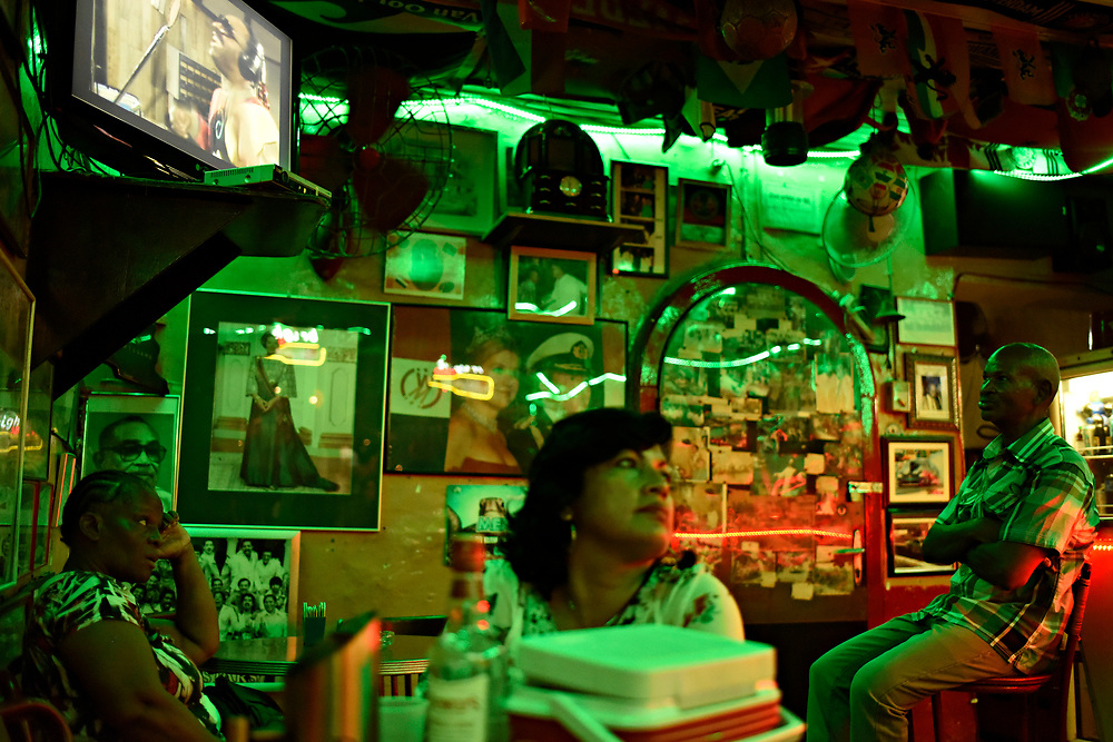 """WILLEMSTAD, CURACAO - DECEMBER 12, 2014: Established in 1954, one of Curacao's oldest bars, the Netto Bar in Otrobanda, is a popular local watering hole, discovered by tourists and visited by Dutch royalty. It's decorated with pictures of Dutch King Willem-Alexander and Dutch soccer paraphernalia and known for it's Rom Berde (green run served with coconut water). Netto's protege and the bar's current owner Chu Zimmerman, right, sits for a moment to watch the """"We Are The World"""" video on TV.  (photo by Melissa Lyttle)"""