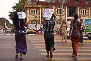 A group of people carry books through the streets of Yangon, Burma.<br />