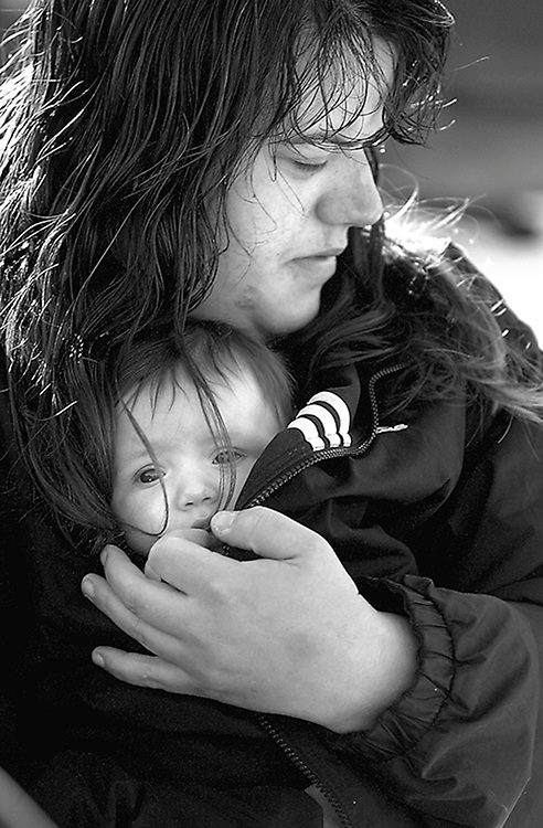 Karen Sanders tries to keep her one-year-old daughter, Kerri, warm while watching their house burn on Christmas Day in Owensville. Family members were asleep when the fire began in the living room around the Christmas tree. Everyone got out safely, but lost everything in the fire.