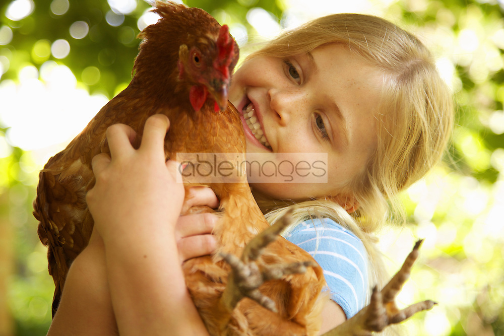 Smiling Girl Hugging Chicken