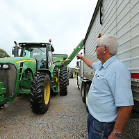 Tony Campbell guides the driver into place before off loading a trailer full of soybeans.