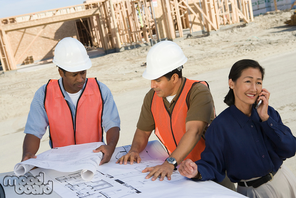 Two construction workers looking at blueprints and architect talking on phone on construction site