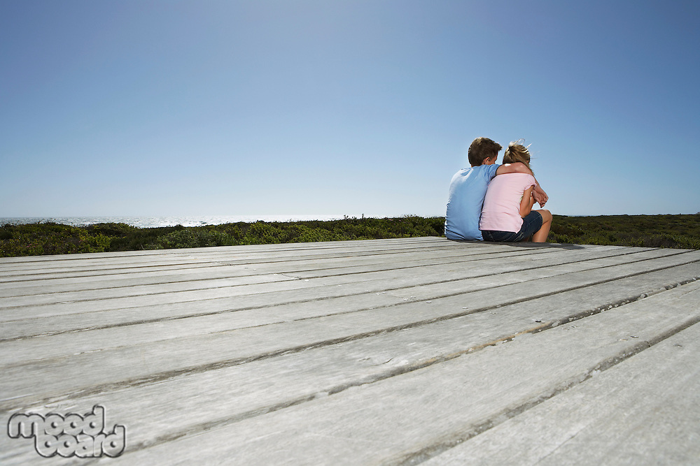 Young boy with arm around young girl sitting on boardwalk