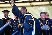 Comedian and actor Bill Cosby waves after he receives an honorary degree following the commencement address during graduation ceremonies at the George Washington University May 18, 1997 in Washington, DC.