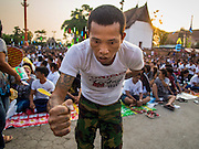 "07 MARCH 2015 - NAKHON CHAI SI, NAKHON PATHOM, THAILAND:  A man channeling the power of his spiritual tattoo goes to the stage at the Wat Bang Phra tattoo festival. Wat Bang Phra is the best known ""Sak Yant"" tattoo temple in Thailand. It's located in Nakhon Pathom province, about 40 miles from Bangkok. The tattoos are given with hollow stainless steel needles and are thought to possess magical powers of protection. The tattoos, which are given by Buddhist monks, are popular with soldiers, policeman and gangsters, people who generally live in harm's way. The tattoo must be activated to remain powerful and the annual Wai Khru Ceremony (tattoo festival) at the temple draws thousands of devotees who come to the temple to activate or renew the tattoos. People go into trance like states and then assume the personality of their tattoo, so people with tiger tattoos assume the personality of a tiger, people with monkey tattoos take on the personality of a monkey and so on. In recent years the tattoo festival has become popular with tourists who make the trip to Nakorn Pathom province to see a side of ""exotic"" Thailand.  PHOTO BY JACK KURTZ"