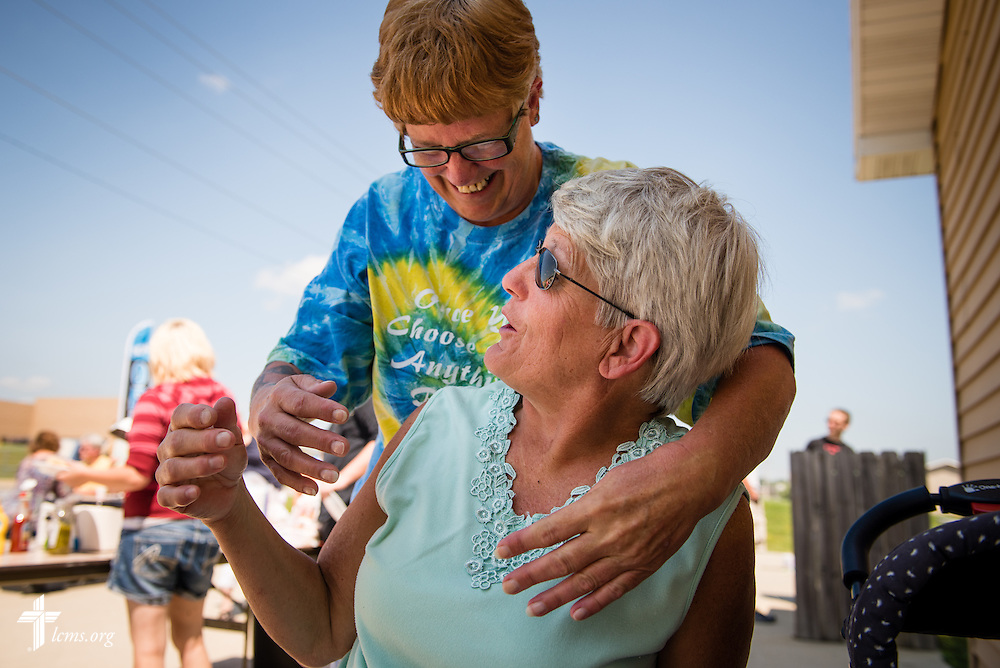 Dellene Smith (standing) greets her sister Eleanore Henry during the grand opening of the Iowa Life Care (LC) Clinic  on Saturday, Aug. 15, 2015, in Creston, Iowa. The clinic is a former Planned Parenthood facility. LCMS Communications/Erik M. Lunsford