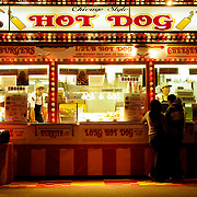 Maria Alondra, 16, and Brian Maldonado, 17, of Indio, California, cuddle in the cold as they await dinner at a hotdog stand at the Riverside County Fair and National Date Festival, in Indio, California on February 13, 2009. The staff inside the stand, Salvador Mendoza, left, and Lori White, right, keep warm at work among the heat lamps.   Photo by Jen Klewitz