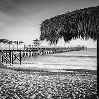 San Clemente pier and tiki umbrella black and white photo. San Clemente is a popular beach city in Orange County Southern California in the United States of America. Copyright ⓒ 2017 Paul Velgos with all rights reserved.
