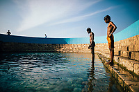 Jaffna, Sri Lanka -- February 8, 2018: Young boys swim and dive at the Keerimalai Springs, sacred pools fed by sea waters on the northern shores of the Jaffna Peninsula.