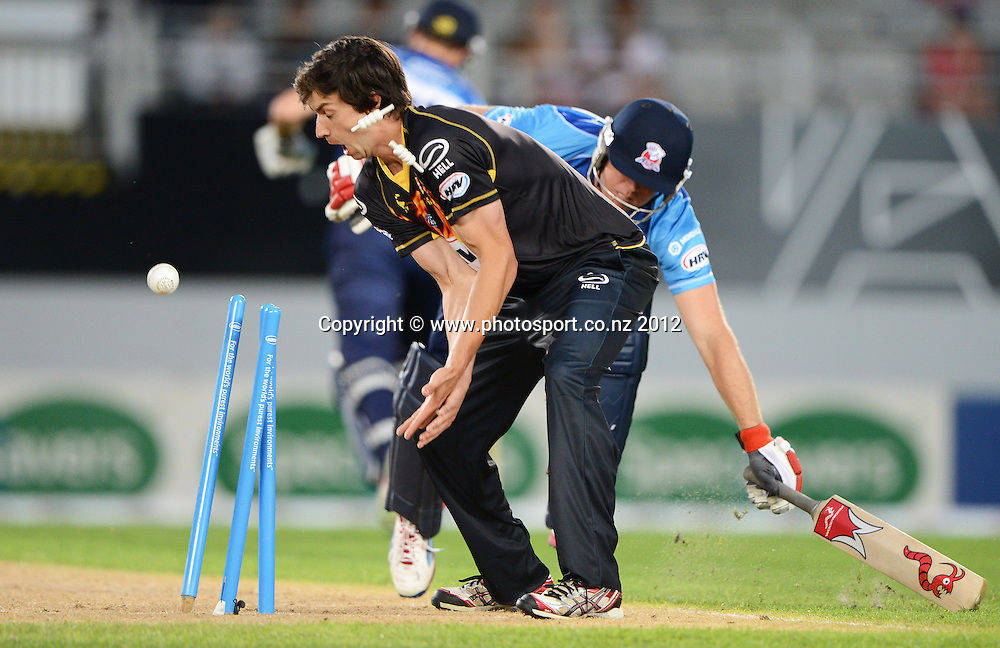 Lou Vincent is run out after a direct hit by Grant Elliott as bowler Mark Houghton looks on during the HRV Cup Twenty20 Cricket match between Auckland Aces and Wellington Firebirds at Eden Park on Friday 28 December 2012. Photo: Andrew Cornaga/Photosport.co.nz
