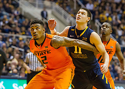 Oklahoma State Cowboys guard Le'Bryan Nash (2) fights with West Virginia Mountaineers guard Nathan Adrian (11) for space on a rebound during the second half at the WVU Coliseum.