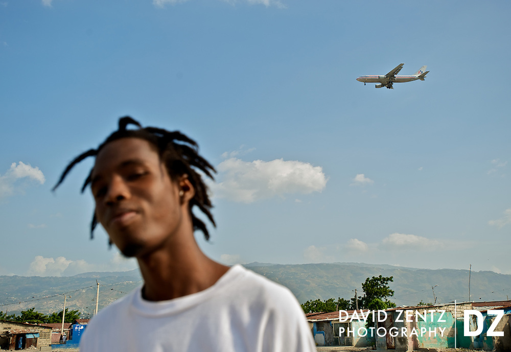 2Double stands near his home in the infamous slum of Cite Soleil as an American Airlines flight, likely carrying visiting members of the diaspora and social workers, flies overhead on July 19, 2008.
