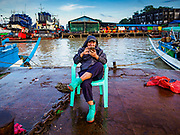 23 NOVEMBER 2017 - YANGON, MYANMAR:  A fish buyer checks his smart phone on a pier at the San Pya Fish Market. San Pya Fish Market is one of the largest fish markets in Yangon. It's a 24 hour market, but busiest early in the morning. Most of the fish in the market is wild caught but aquaculture is expanding in Myanmar and more farmed fresh water fish is being sold now than in the past.   PHOTO BY JACK KURTZ