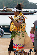 Aunofo in lei and traditional ta'ovala, with children at homecoming greeting for Aunofo, crew member on traditional double-hulled Polynesian voyaging canoe or waka, Hine Moana (in background), at Hunga Village, Hunga Island, Vava'u, Kingdom of Tonga, South Pacific