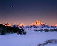 Winter sunrise and full moon setting over the Teton Range Grand Teton National Park Wyoming USA