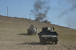 Licensed to London News Pictures. 20/02/2017. Albu Saif, Iraq. An armoured Humvee of the Iraqi Emergency Response Division and an M117 armoured personnel carrier of the Federal Police drive into a valley as security forces prepare to carry out a flanking assault on the village of Albu Saif, Iraq.<br /> <br /> The settlement of Albu Saif is located on high ground overlooking Mosul Airport and as such is a strategic point that needs to be taken as part of the operation to retake the western side of Mosul. Photo credit: Matt Cetti-Roberts/LNP