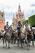 Mexican cowboys ride past the Parroquia de San Miguel Arcangel church at the end of their pilgrimage during the festival of Saint Michael in San Miguel de Allende, Mexico.