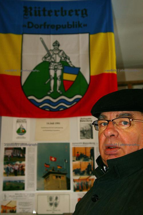 """Der ehemalige Bürgermeister Meinhard Schmechel vor der historischen Flagge der 1989 ausgerufenen """"Dorfrepublik Rüterberg"""". Aufgrund dieser Abschottung etablierte sich die Bezeichnung """"Dorfrepblik"""" für den kleinen Ort bei Dömitz (Mecklemburg-Vorpommern)."""