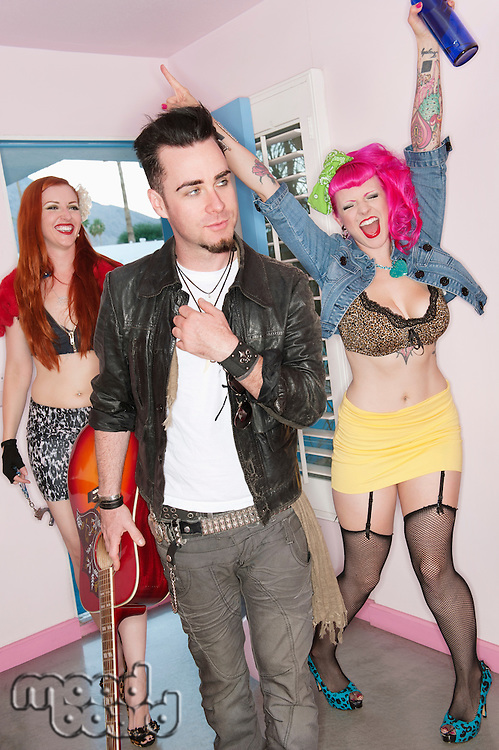 Handsome man holding guitar with women standing in background