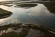 Aerial view of a boat passing through the marsh in Charleston, SC