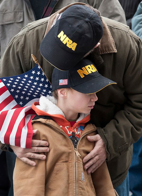 "Gun rights supporter Kenny Deal of Stafford, Conn., hugs his son Daniel, at rally at the Capitol in Hartford, Conn., Saturday, Jan. 19, 2013.  The rally, dubbed, ""Guns Across America"", at Connecticut's state Capitol and state capitol buildings across the country to raise concerns about possible new gun legislation that could affect gun owners' rights in the wake of the Dec. 14 school shooting at Sandy Hook Elementary School in Newtown. (AP Photo/Jessica Hill)"