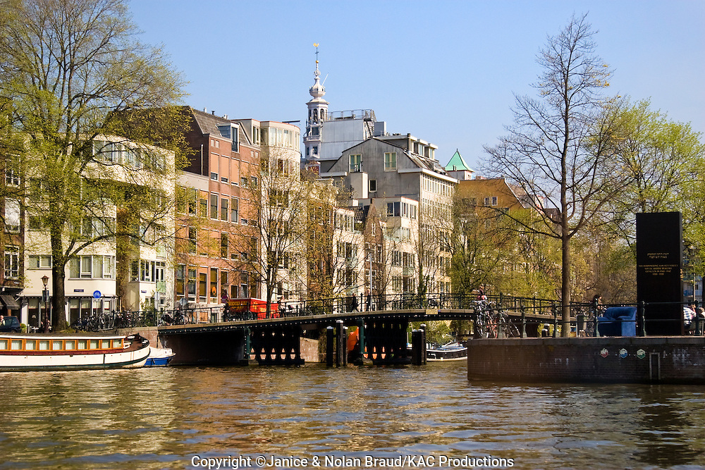 Downtown Amsterdam in The Netherlands. The cities of Holland generally are built around canals and boats are a major means of travel in Holland.