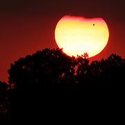June 5, 2012 - Lexington, Kentucky, USA - The planet Venus can be seen as a small black dot as it crosses in front of the setting sun on Tuesday, June 5, 2012. The planet's transit across the sun, which lasted over 6 hours, will not be seen again until 2117. The transit began at around 6 p.m. EST and could be viewed until the sun set at around 9 p.m.  Photo by David Stephenson