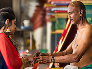 27 DECEMBER 2015 - SINGAPORE, SINGAPORE: A Hindu priest (right) prays with devotees at the Sri Mariamman Temple in Singapore. The Sri Mariamman Temple is Singapore's oldest Hindu temple. It is an agamic temple, built in the Dravidian style. The temple is in the downtown Chinatown district, and serves Hindu Singaporeans and Tamilians. Due to its architectural and historical significance, the temple has been gazetted a National Monument and is a major tourist attraction. The Sri Mariamman Temple was founded in 1827 by Naraina Pillai, eight years after the East India Company established a trading settlement in Singapore.       PHOTO BY JACK KURTZ
