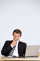 Businessman picking nose, looking at laptop in office