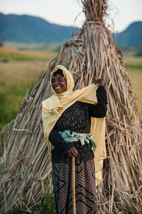 Zemu Ali stands next to her small shelter where she guards the teff crop of a local farmer. The small stalk-built structures are common in the region south of Kombulcha where large amounts of teff are grown in the Ethiopian highlands. Teff is highly valued, and Zemu is making sure that stray cattle do not invade the field and damage the crop.