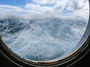 A wave rises outside a ship portal window in the rough waters of 400-mile-wide Drake Passage, on a cruise to Antarctica from Ushuaia, Argentina, South America.